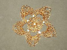 Flor em croche de fio de metal,  cobre esmaltado em dourado, bordado com strass.