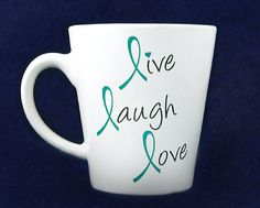 "These teal ribbon coffee mugs say ""Live, Laugh, Love"" where the L's are teal ribbons. Each 12 ounce ceramic coffee mug comes in a gift box and is dishwasher safe. This is a wholesale pack that contains 12 mugs Case)."