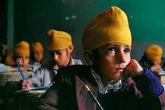 Kabul, Afghanistan. This photo caught my interest because of the leading line the yellow turbans created and the eyes of the boy. They pull you in, and create the central focus of the photo.