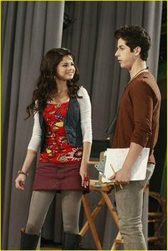 Selena Gomez as Alex Russo || white 3/4 scoop neck top, red floral spaghetti strap top, dark vest, maroon denim skirt, gray opaque tights, brown leather boots, boho bracelet, flower ring || Wizards of Waverly Place