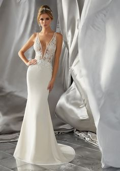 This Sultry Wedding Dress Features a Soft Chiffon Skirt and Crystal Beaded. The bodice is embroidered with a satin trim and a sheer plunging V-neckline.