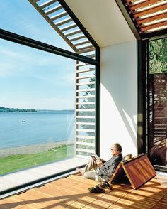 The Trues host parties in the glass-walled structure, located steps from their vacation home, or they escape to it to catch some rays and read a book. Bill reclines on cushions hidden under the reclaimed-fir floorboards that are propped up with Sugatsune hinges.  Photo by: Grant Harder