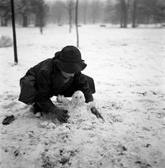 A little boy crouching and making a snowman in a park after a snowfall in Milan in the 1950s.