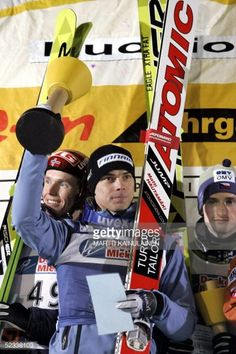 Finland's Matti Hautamaki celebrates on the podium after winning the World Cup Ski Jumping competition next to Norway's Roar Ljoekelsoey and Czech's...