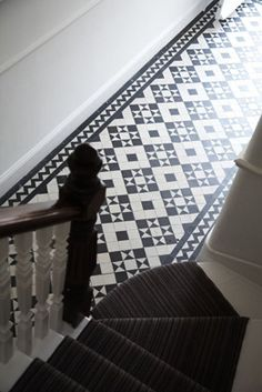 Staircase with charcoal runner, geometric tiled hallway.