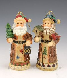 Woodsy Santas-- Great pair of 'bark-look' woodsy Santa ornaments. One Santa figurine holding a birdhouse and cardinal and the other holding a small tree and lantern. Each Santa ornament stands approximately 3.5 inches tall.