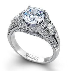 Diamond Halo Engagement Ring Featuring Two Pear Cut Diamonds Weighing 0.47 Carats Total Weight and 0.64 Carat Round Diamonds set in 18K White Gold by Designer Simon G. Available at BenGarelick.com starting at $6100 https://www.bengarelick.com/products/simon-g-18k-white-gold-ring-set-with-2-pear-diamonds-0-47-total-weight-and-0-64-carat-round-diamonds