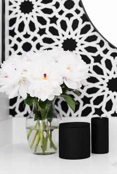 Black and white bathroom with vase of flowers