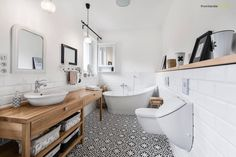 Perfect, beautiful, chic and modern scandinavian inspired bathroom with pattern tiled black and white floor, wooden vanity with baskets, free-standing bath, mirrors and white sink. By: PracowniaPolka.