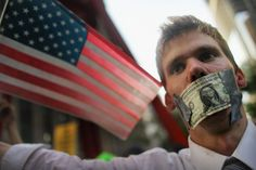 A protester wears a dollar bill over his mouth at the start of a march by demonstrators opposed to corporate profits on Wall Street on September 30, 2011 New York City. (Mario Tama - AFP/Getty Images)