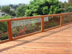 Redwood deck with glass panel railings that easily let in the breathtaking view. Deck designed by Block Island Remodeling.