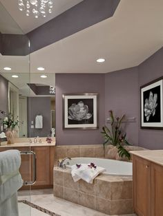 Bathroom Design, Contemporary Bathroom With Purple Bathroom Paint Ideas Also Elegant Bathtub Design With Beige Marble Colors Also Glass Door And White Flower Pictures Hanging On The Wall With Stainless Picture Frames: Bathroom Mirrors Ideas with Lighting Combination