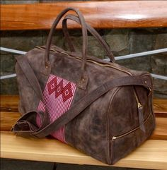 Luxurious brown Ethiopian leather sits next to a hand woven cotton pattern. Multiple interior zip pockets, and unique patterns to last you many a weekend away.