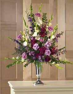 This urn arrangement contains flowers such white gladiolus, purple delphinium, purple larkspur, burgandy stock, burgandy carnations, laven...