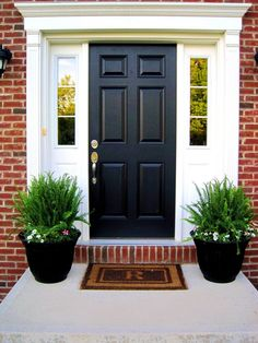 Black front door with two green planters and white trim on brick house. Paint your front door black and make it stand out with an updated look. Curb appeal painting your front door black. Front Porch Plants, Front Porch Flowers, Front Door Porch, Front Door Entrance, Front Entrances, Front Door Decor, Porch Doors, Main Entrance, Front Porches