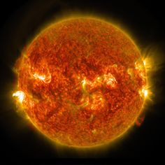 The sun emits an M5 flare, seen on the left, August 24, 2014