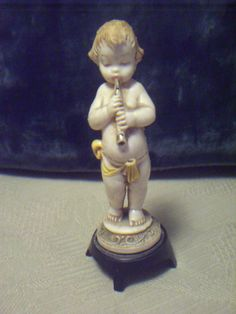 Depose Italy, Figurine with spider mark, Cherub on a base playing a cornet