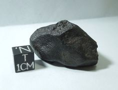 Unclassified stony meteorite recovered from the Saharan Desert in Morocco. Black fusion crust and regmaglypts. Whole, uncut stone. 42 grams. See it at Galactic Stone and Ironworks.