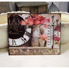 Termometr na typowo prowansalskim obrazie, z motywem różowych tulipanów w konewce oraz zegar. Obrazek jest uroczy, pokazuje że termometr może jednak pięknie wyglądać.