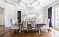 Chic dining room boasts a geometric coffered ceiling accented with an oval fringe chandelier illuminating a zinc top trestle dining table lined with purple Frenchd ining chairs - complete with monograms, as well as gray velvet wingback dining chairs placed at each end of the table.