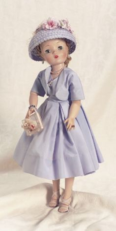 """Cissy in Lavender Afternoon Gown 20"""" (51 cm). Blonde hair with two spit curl bangs,side hair drawn into cluster of curls at nape of neck. Wearing afternoon party dress comprising lavender taffeta dress with fitted bodice,triple-box-pleated skirt and short matching jacket,lavender straw bonnet with veil and floral trim,nylon petticoat with pink rick- rack tulle double ruffle,panties,stockings,lavender and purple sling heels,pearl necklace and teardrop earrings,amethyst and silver bracelet and rin"""