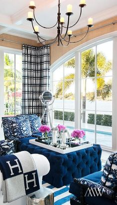 Contemporary living room features a coffered ceiling accented with an iron chandelier over a white roll arm sofa drape din a blue hermes blanket facing a blue velvet tufted ottoman used as a coffee table flanked by black abacus chairs covered in blue floral cushions atop a blue striped rug.