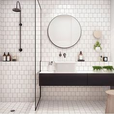 This simple, yet stunning bathroom features white subway tiling with grey grout, wall hung vanity and finished off with a round statement mirror.