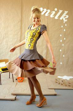 Süßes und gleichzeitig elegantes Kleid aus grauem Viskosejersey mit einem Muster aus 70er Blüten und Blumen in gelb-grau-beige Tönen. Der Rock ist dre