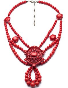 """A red statementnecklace with beaded strands and red metal center. Wear this necklace withwhite, navy or black for an eye-catching contrast appeal. 18"""" long ba"""