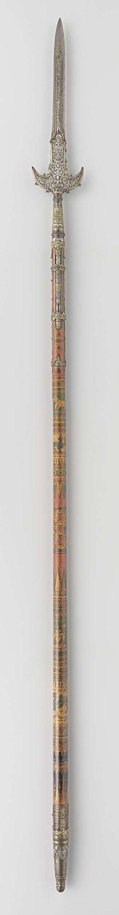 | Partizaan van het wapenrek door Indische groten geschonken aan Gouverneur-Generaal J.C. baron Baud, c. 1700 - c. 1800 | Zeer grote met zilver beslagen partizaan, de schacht beschilderd in zwart, rood, geel en groen met voorstellingen van olifanten, boddhisattva's, menselijke figuren en geometrische motieven op de punt en het beslag in reliëf Boddhisattva's, ranken, menselijke figuren en monsterkoppen. Bovenaan de schacht drie zilveren banden met robijnen ingezet.