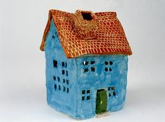 The children roll clay slabs to construct houses. For ages 9 to 13. Plan 6 sessions.