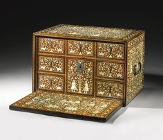 An Indo-Portuguese ivory-inlaid cabinet, Gujarat or Sind, 16th century decorated throughout with ivory and green and brown-stained ivory with an abundance of figures and animals in various activities, notably, men riding elephants, on horseback, men and women conversing under a tree, men in European (probably Portuguese) costume riding and holding a lance, the top with winged senmurvs carrying away small elephants, the hinged lid opening to reveal six drawers disguised as eight, decoration…