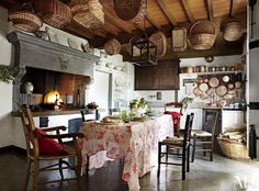 The original kitchen hearth in the historic Italian villa of linens matriarch Dede Pratesi is made of pietra serena, a stone commonly found in Tuscan houses; the table, covered in a vintage Pratesi cloth, is surrounded by 19th-century chairs inherited from her grandparents