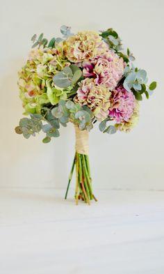 'Bouquet' francés de tonos empolvados, con las flores y elementos vegetales dispuestos en grupos: eucaliptus gunni, clavel antigua y hortensias bicolor de la primera floración. Foto: Llorens&Durán