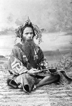 "Japan | ""Ainu man with ikupasuy (prayer stick), Festival of the Ainus, 1901"" | Photographer Dean Bashford"