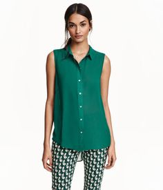 Sleeveless chiffon blouse with a collar, buttons at front, and a rounded hem. Slightly longer at back.