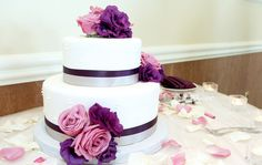 two layer white wedding cake with pink and purple flowers