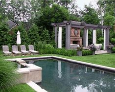 Great pergola with fireplace...love the grass around the pool, too!