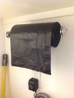 28 Brilliant Garage Organization Ideas ~ garbage bags on a paper towel holder under a cabinet or on a wall. Genius!