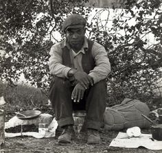 """""""Photograph shows a black hobo, or 'gentleman of the road', as they were called back then. This man is setup at camp, looks like he just got done eating. Photo dates to around 1935 during the Great Depression era. This is part of the photo collection of Dorothea Lange, freelance government photographer."""""""