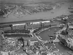 Juni 1950 Luchtfoto van het stationseiland met Centraal Station en Amsterdam Noord. Het station, architect P.J.H. Cuypers, werd gebouwd op drie eilandjes in het IJ op 8387 palen. Koningin Wilhelmina opende het gebouw in 1889. ANP PHOTO G. V.D. WERFF