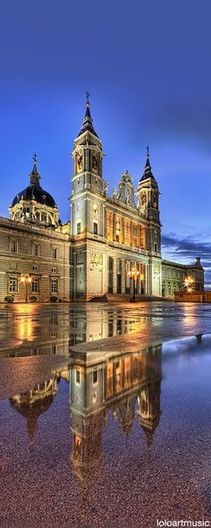 Almudena's Cathedral, Madrid, Spain. What a beautiful photo! The architecture of this splendid Church against  the wet space in front. The lights in this photo shine farther with the water being there. The lights,the time of day the photo was taken,only enhance  this beautiful picture!
