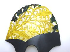 A gorgeous vintage Art Nouveau carved celluloid hair comb in black with translucent yellow. There is also some green paint on the piece.    No