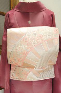 薄桜色と銀を基調にアーチのような優美な曲線を描く源氏車浮かぶ袋帯です。