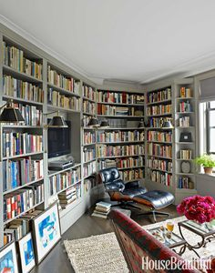 Home library with built-in bookshelves, wall lights and Eames-style midcentury modern recliner
