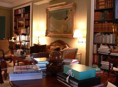 Bunny Williams ~ A Vuillard-style painting hangs above the sofa in the book-filled library/dining room of her NYC home.