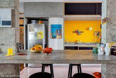 uma cozinha integrada, com vigas e colunas de concreto à mostra, parede amarela e piso de granilite rosa