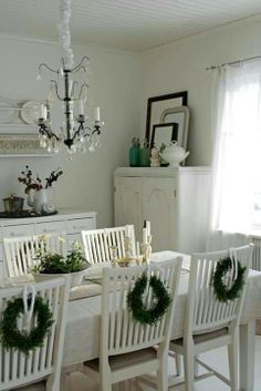 Mini Christmas wreaths attached to back of chairs bringing just the tiniest amount of colour to this (mostly white) contemporary space . . .