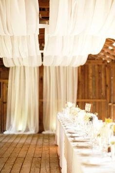 Yards of draped white fabric softens the interior of a barn wedding reception. debenlow