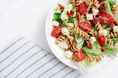 Overhead, close-up shot of BLT pasta salad with crispy bacon, grape tomatoes, green leafy lettuce and fresh mozzarella in white bowl with blue striped linen. Shutterstock ID Purchase Order: N/A Asian Pasta Salads, Mediterranean Pasta Salads, Caprese Pasta Salad, Summer Pasta Salad, Blt Salad, Salad Recipes Video, Pasta Salad Recipes, Pasta Integral, Shrimp And Quinoa